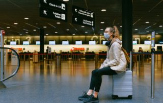 Woman wearing protective mask, seated at airport on her luggage