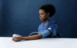 Seated healthcare professional taking her own blood pressure with a blood pressure monitor